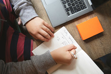 A Teenage Boy Is Calculating His Budget Per Month Using A Notebook And Laptop At His Desk