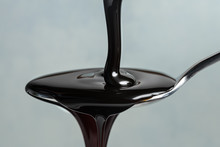 Close-up Of Molasses Syrup Pouring In Spoon Against Gray Background
