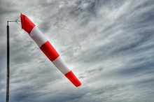 Low Angle View Of Windsock Against Cloudy Sky