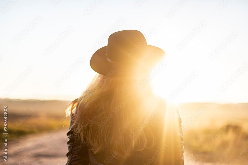Fototapeta Girl in sunny light with long hair in black hat on beautiful sandy road looks at sunset. Outside. View from backside. Warm sunny day. Travel concept. New life, new horizons and opportunities