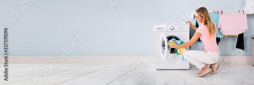 Vászonkép Woman Putting Clothes In Washing Machine