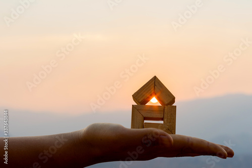 Cuadros en Lienzo Hands holding house sunset background, Real estate investment is a business to build a house to sell to buyers in the market through agents