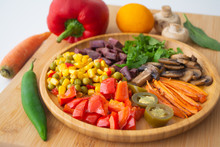 Nutritious And Healthy Buddha Fajita Bowl With Sweet Corn, Green Peas, Red Bell Pepper, Jalapenos, Carrots, Mushrooms, Spinach, Beetroot And Sweet Potatoes Surrounded By Ingredients And Lemon