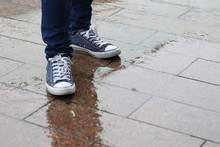 Low Section Of Man Standing On Wet Sidewalk