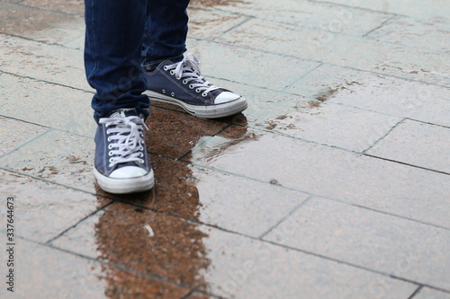 Canvas Low Section Of Man Standing On Wet Sidewalk