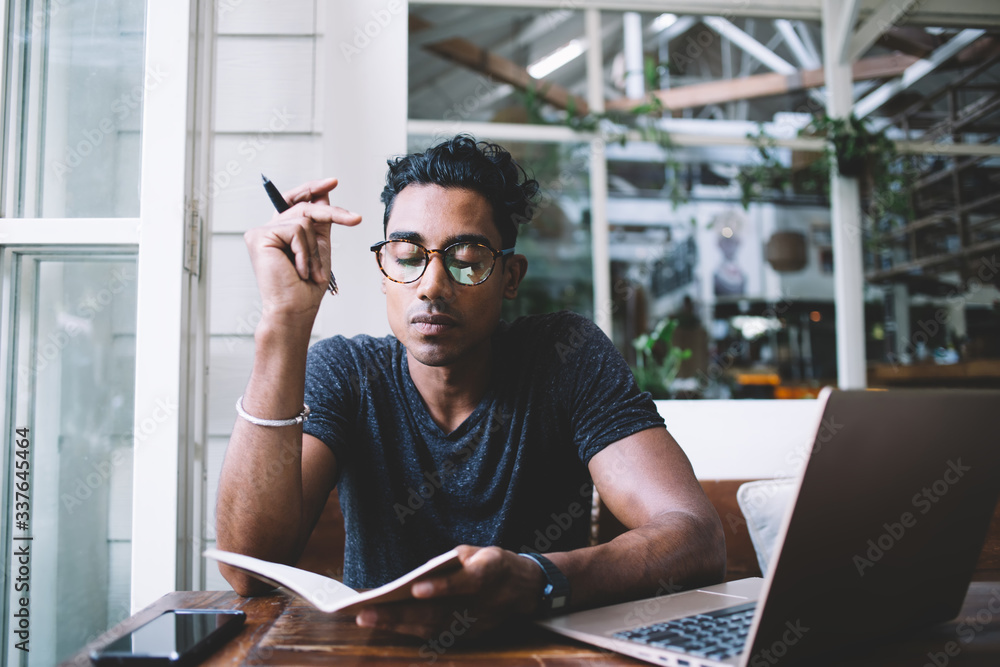 Fototapeta Thoughtful ethnic writer writing in journal while sitting at table with gadgets