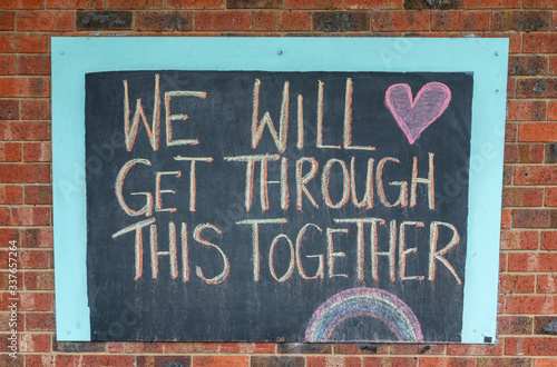 Obraz Chalk sign saying we will get through this together on a brick wall.  Written during the Coronavirus pandemic lockdown. - fototapety do salonu