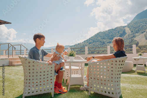 Fototapeta Beautiful young family, parents and little daughter, on the opened terrace in the white wicker furniture with great mountain view backwards, sunny day, blue sky obraz na płótnie