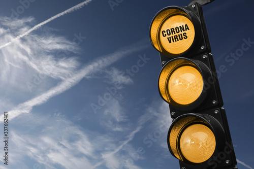 Fotografering Semaforo con tre luci gialle accese e scritta corona virus su cielo  azzurro con