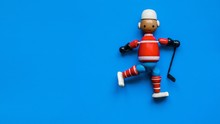 Close-up Of Wooden Toy Figurine Over Blue Background