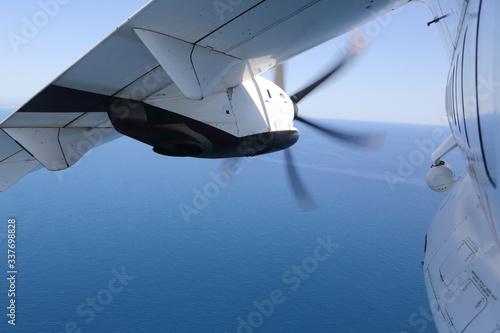 Fotografie, Tablou Ala e motore di aereo turboelica sopra il mare