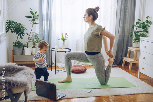 Fotografie, Obraz Women exercise yoga while her baby son exploring living room
