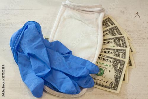 Fototapeta Ludzka ręka w niebieskiej rękawicy ochronnej trzymającej pakiet banknotów i maskę ochronną. obraz