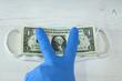 Ludzka ręka w niebieskiej rękawicy ochronnej trzymającej pakiet banknotów i maskę ochronną.