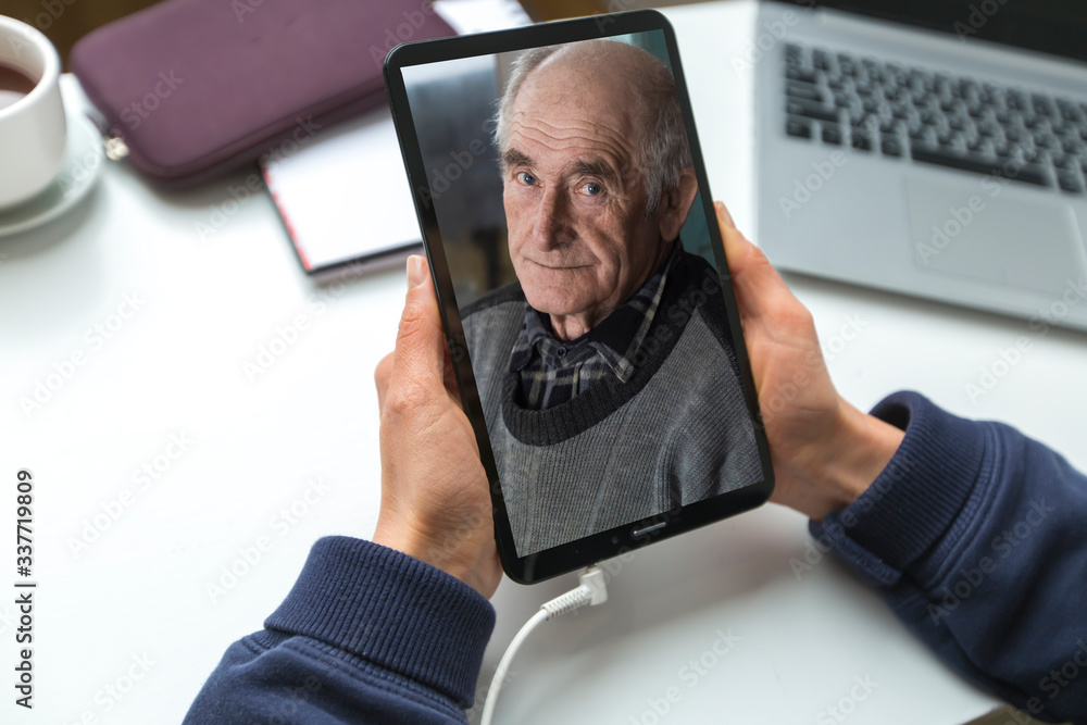 Fototapeta Conversation in a video chat online with his father, an old man, a senior. Remote communication with the elderly, support and assistance.
