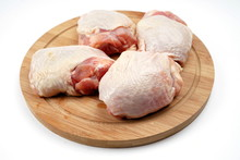 Fresh Chicken Thighs On A Chopping Board. Isolate On A Light Background
