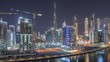 Skyline view of big city with bright roads and streets and high skyscrapers of Business Bay and Downtown at night near canal aerial timelapse, Dubai, United Arab Emirates
