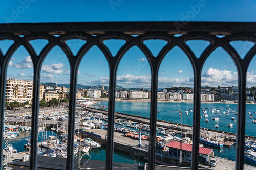 Historic center of the city of San Sebastián in Donostia, Guipúzcoa, Basque Country, Spain. La Concha beach seen from behind a black cast iron railing. The sky is blue and cloudy.