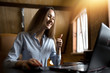 A young woman waving his hand in greeting. Conversation by video conference from home. Sign husky and okay.