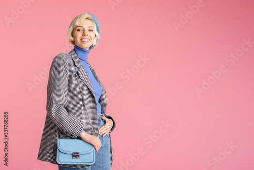 Fashion portrait of elegant happy smiling model wearing trendy outfit: houndstooth print blazer, beret, with   stylish light blue faux leather shoulder bag, posing on pink background Wallpaper Mural
