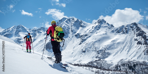 Fotografía Two active men ski touring on mountain skis and splitboard at sunny winter day