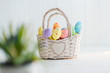 Multi-colored Easter eggs in a basket on a white wooden background