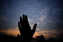 Cropped Image Of Silhouette Hand Against Sky At Sunset