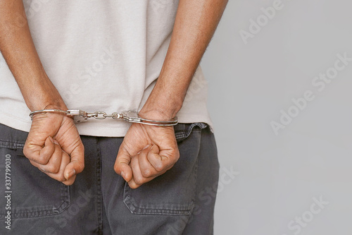 Photo Arrested man handcuffed hands at the back isolated on gray background