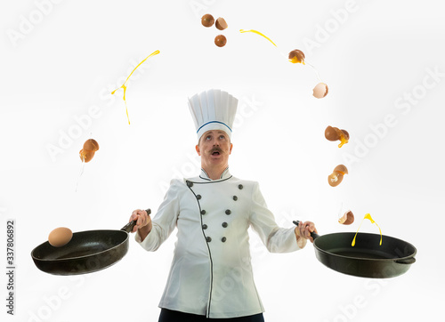 Foto The cook juggles eggs in a frying pan