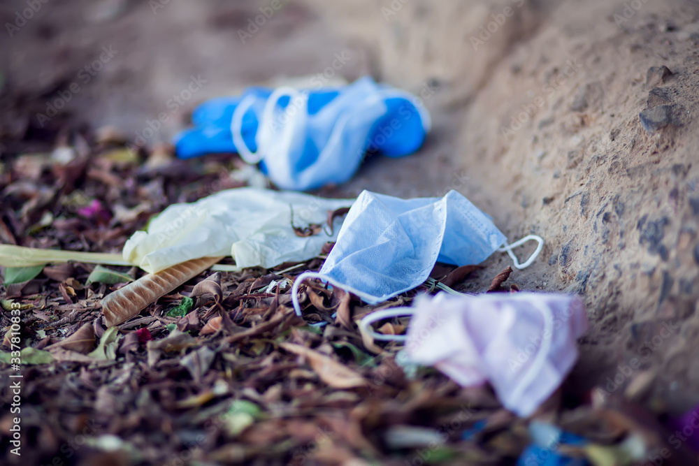 Fototapeta Used medical face masks and gloves on the ground outdoor. Environmental pollution concept