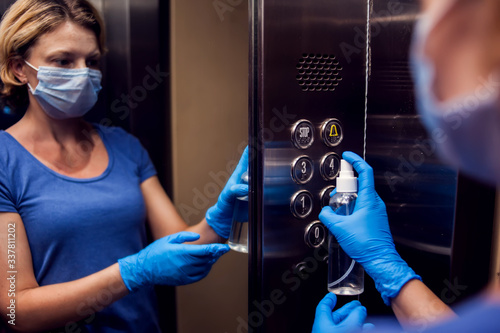 Canvastavla Woman with face medical mask and gloves doing disinfection of buttons in elevator