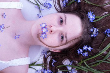 innocent girl lies in hair tangled blue spring flowers
