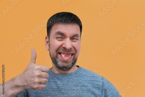 cheerful charismatic bearded young man with no front upper teeth gives a thumbs Wallpaper Mural