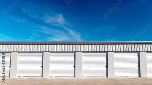 Fotografie, Obraz Mini storage garages lines up next to one another with blue sky and clouds