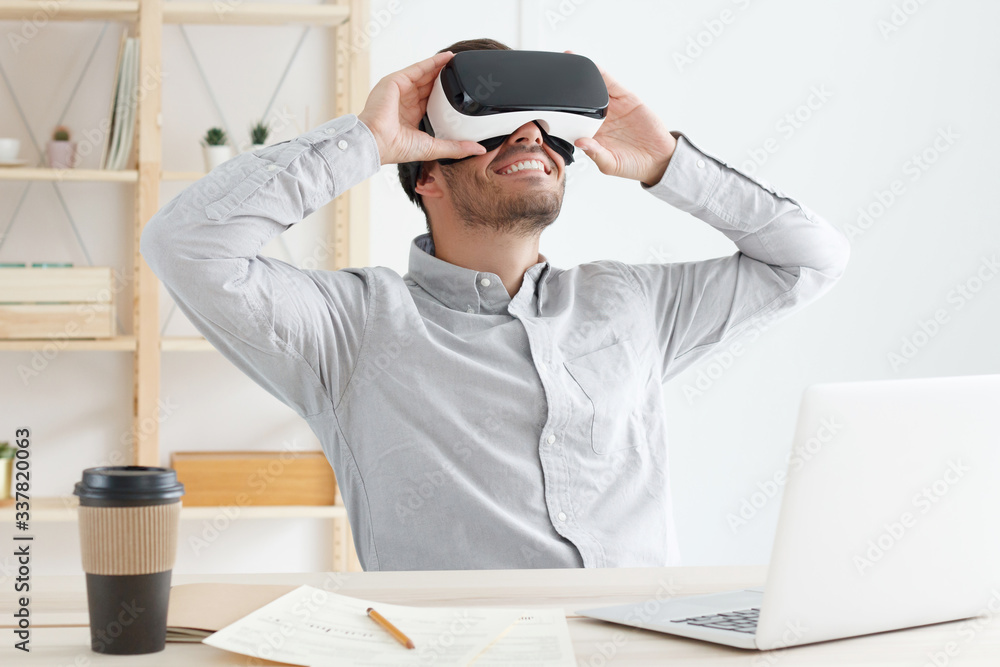 Fototapeta Young IT guy wearing gray shirt and virtual reality headset, sitting in office and experiencing VR opportunities of 3D gaming, smiling happily