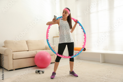 Canvastavla Lazy young woman with hula hoop and smartphone at home