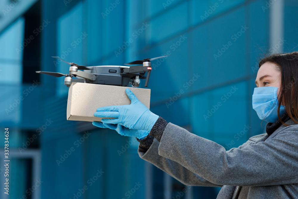 Fototapeta Young woman in gloves and mask sends a package with drone