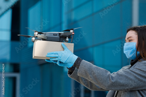 Fototapeta Young woman in gloves and mask sends a package with drone obraz