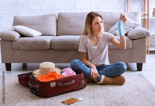 Things in suitcase for vacation. Woman with mask in hands Canvas Print