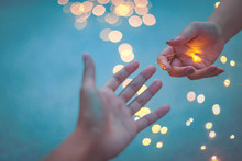 Cropped Hand Of Woman Giving Illuminated String Light To Man