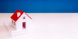 canvas print picture - white paper miniature house with red roof on blue color background