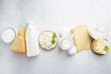 Fresh Dairy Products, Milk, Cottage Cheese, Eggs, Yogurt, Sour Cream And Butter On White Table, Top View