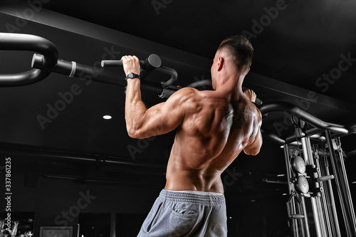 Photo The athlete does a pull-up on the horizontal bar