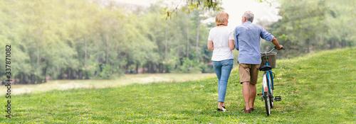 Fototapeta Elder healthy leisure lifestyle,Senior couple walking their bike along happily talking in the park, rear view of an older caucasian walk in a park, Banner image, Health care insurance obraz