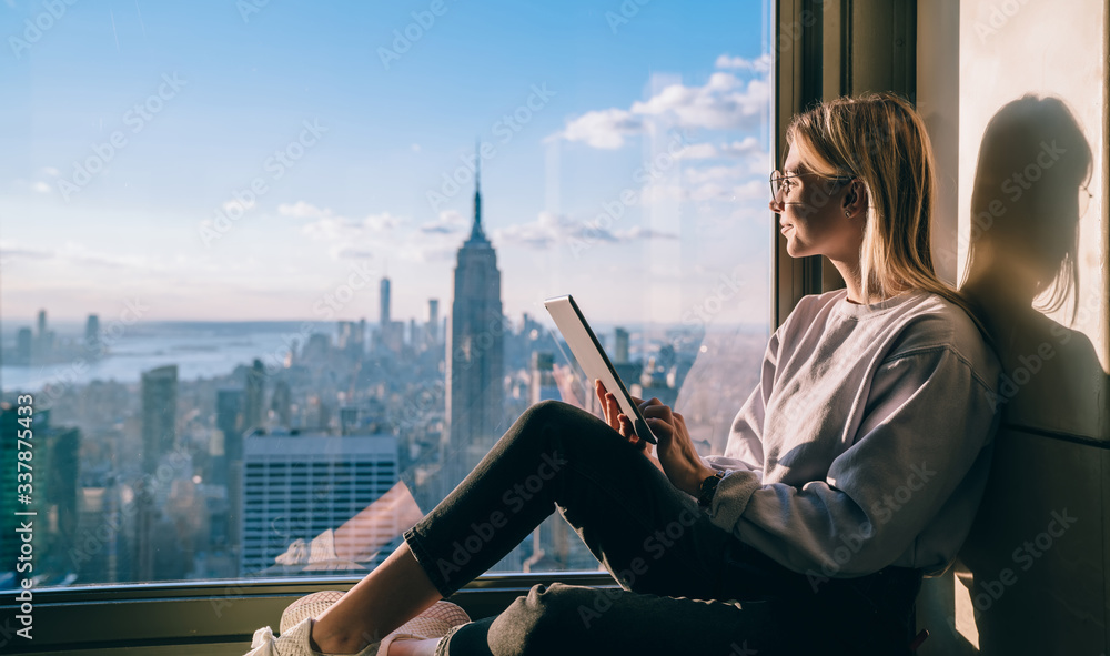 Fototapeta Side view of happy millennial digital nomad with modern touch pad looking in lookout window and dreaming about New York sightseeing, carefree hipster girl enjoying time in high rise building