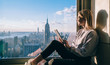 Side view of happy millennial digital nomad with modern touch pad looking in lookout window and dreaming about New York sightseeing, carefree hipster girl enjoying time in high rise building