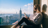 Fototapeta Nowy Jork - Side view of happy millennial digital nomad with modern touch pad looking in lookout window and dreaming about New York sightseeing, carefree hipster girl enjoying time in high rise building