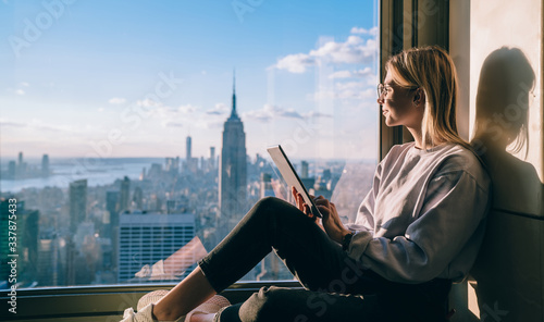 Fotografia Side view of happy millennial digital nomad with modern touch pad looking in loo