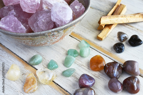 A top view image of rose quartz and various energy healing crystals on a white wooden table Canvas