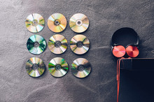Compact Discs Decorated Over Wall By Headphones On Shelf